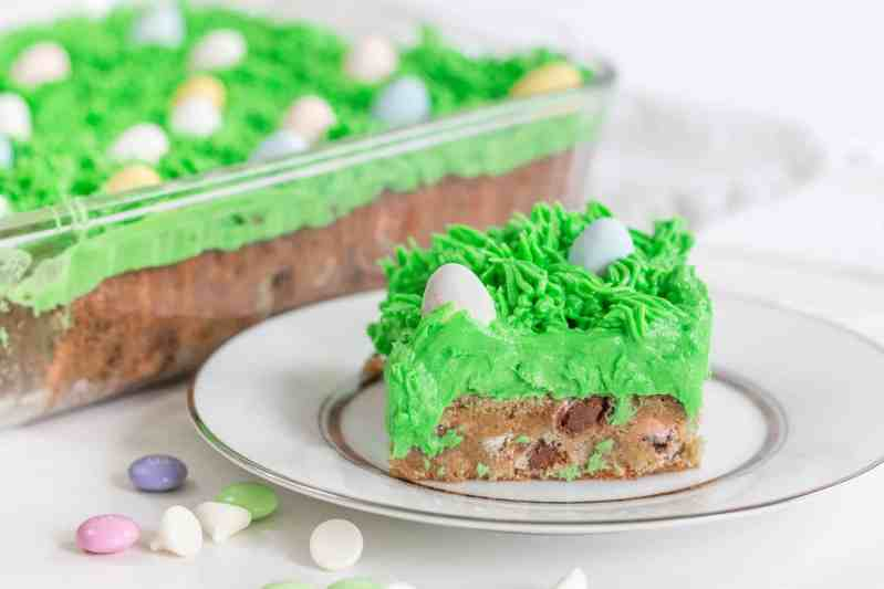 Slice of easter bar blondie on a white plate with green grass icing