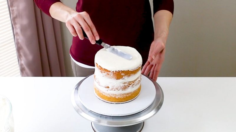 adding buttercream to the top of bottom cake tier