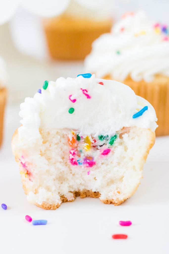 Funfetti Filled Cupcake with bite taken out with cupcakes in background