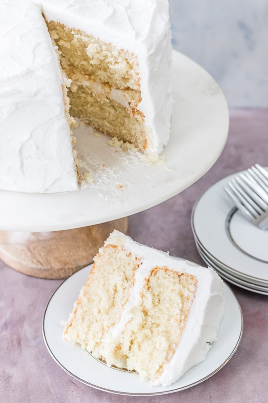 Moist white cake on a cake stand with slice on a white plate