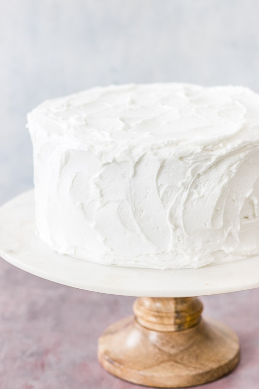 Moist white cake on marble and wood cake stand