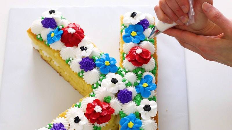 Adding buttercream berries to initial cake