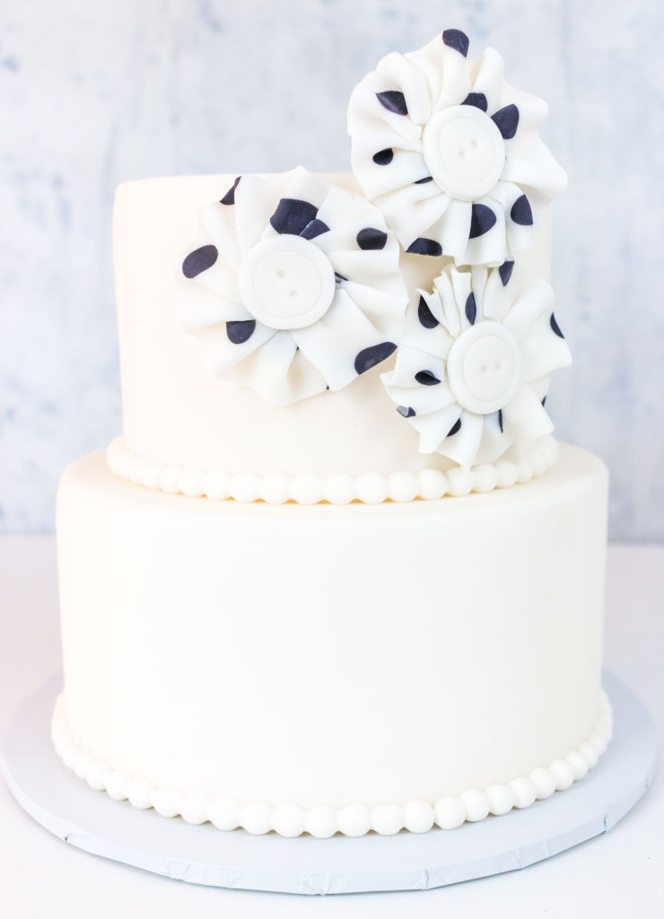 Polka dot fondant fabric look flowers on two tiered ake