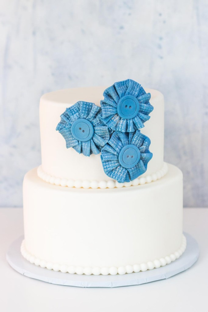 White two tiered cake with blue jean look fondant fabric flower