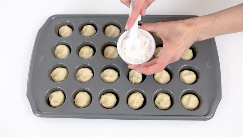 Dipping measuring spoon in flour to make cookie cups