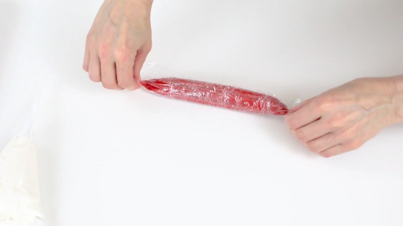 Rolling up red buttercream in saran wrap