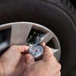 Mechanic Checking Tire Pressure Using Gauge