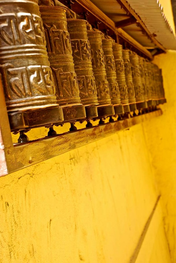 A line of Prayer wheels with the Buddhist Mantra - 'Om Mani Padme Hum' inscribed on it