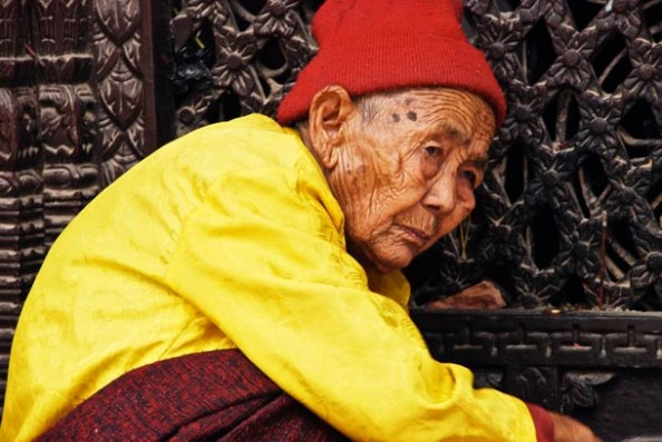A very old lady sitting close to the Stupa Door and chanting prayers