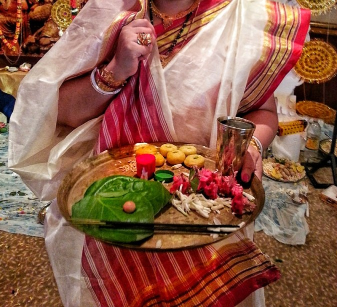 A Bengali lady adorned in traditional red and white sari and holds a puja thali