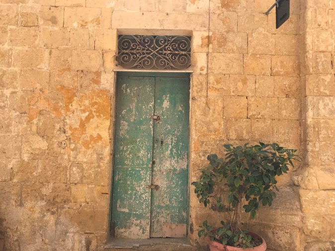 Colourful doors and golden limestone walls in traditional Birgu houses