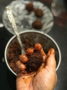 Rolling the coconut-jaggery mixture into truffles
