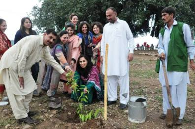 Ms Fauzia Minallah, chief guest of the event, planting a new sapling to encourage planting and caring for trees.