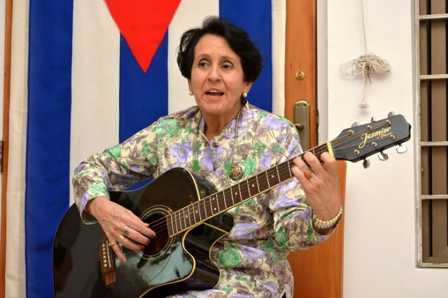 Madame Concepción, wife of Cuban Ambassador, Jesús Zenén Buergo Concepción, playing guitar and singing at the art exhibit by 30 Cuban artists in Islamabad, Pakistan.