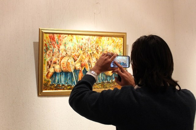 A man takes photo of artwork by Russian diplomat Mr. Youri Kozlov at COMSATS Art Gallery in Islamabad. Photo by Sana Jamal