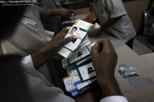 Libyans have their passports stamped as they wait to board a plane from Tripoli's Mitiga airport to Saudi Arabia to perform the annual Muslim Hajj pilgrimage in the holy city of Mecca. Nov. 1, 2011. (Joseph Eid - AFP/Getty Images)