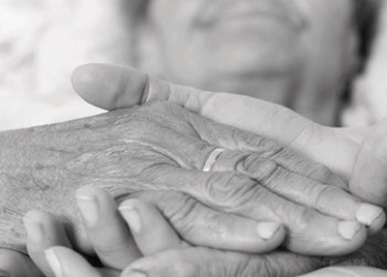 Caring nurse holding kind elderly lady's hands in bed. ** Note: Shallow depth of field