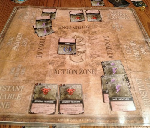 The Dueling Grounds game board clearly delineates ares of play for all combatants. The flip side has similarly clever organizational spaces for deck-building.