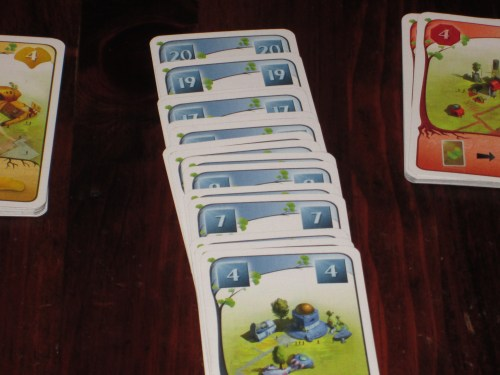 The starting deck has cards representing the letters A-L and the buildings 1-3 of each color. In addition, cards get added to the deck throughout the game. Each color has cards and tiles numbered 4-20 that, when added to the city, get added to the deck, offering new opportunities for building.