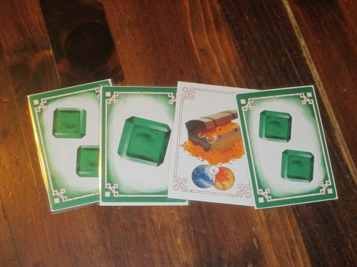 A sample set of emeralds. Sets have to have at least three objects when you first lay them down, and you can only extend a set with at least two objects more. This makes players reconsider simply melding once they have the cards.