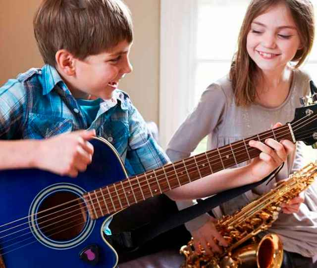 Children Playing Guitar And Saxophone And Having Fun In Their Music Classes At International School Of