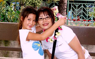 little girl hugging ISP student wearing a lei