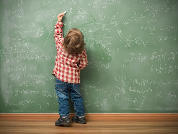 Little boy writing on green blackboard