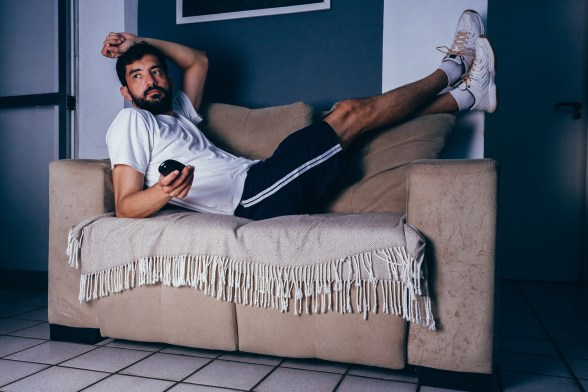 Man wearing sportswear lying on couch watching TV, being lazy.