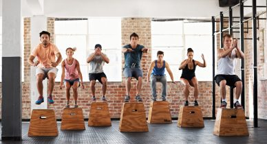 People jumping on boxes at a gym.