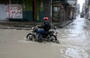 A Palestinian man rides his a bike through a rain flooded street at the Shati refugee camp in Gaza City, Sunday, Jan. 30, 2011. Photo by Mohammed Othman/Flash90