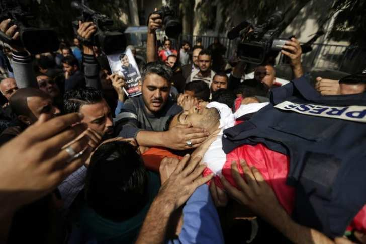 Mourners and journalists carry the body of Palestinian journalist Yasser Murtaja, shot by Israeli forces, during his funeral in Gaza City on April 7, 2018. More info here