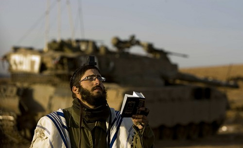 An Israeli soldier prays before entering the Gaza Strip in January.