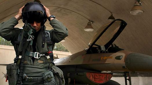 An Israeli jet fighter pilot readies his helmet in a hangar as he prepares to go on a sortie in his F-16 fighter.