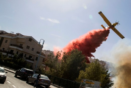 An Israeli firefighter plane helps extinguish a bushfire in the northern Israeli port city of Haifa on November 24, 2016. Hundreds of Israelis fled their homes on the outskirts of the country's third city Haifa with others trapped inside as firefighters struggled to control raging bushfires, officials said. / AFP PHOTO / JACK GUEZ
