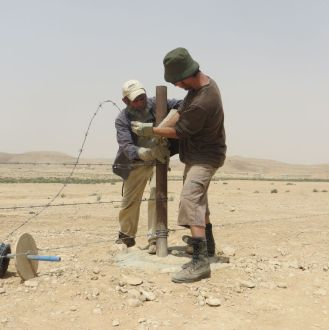 Yoni and Haggai stretch the wire on the fencing posts
