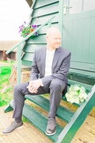 Bruidegom zit op trap van molen
