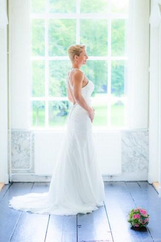 Bruid poseert voor het raam op blauwe vloer