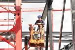 Monteur staalbouw in bak van hoogwerker tussen staal bij Ziggo dome Amsterdam