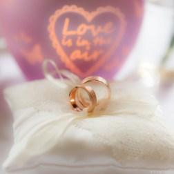 Twee trouwringen op kussentje met hartje op de achtergrond