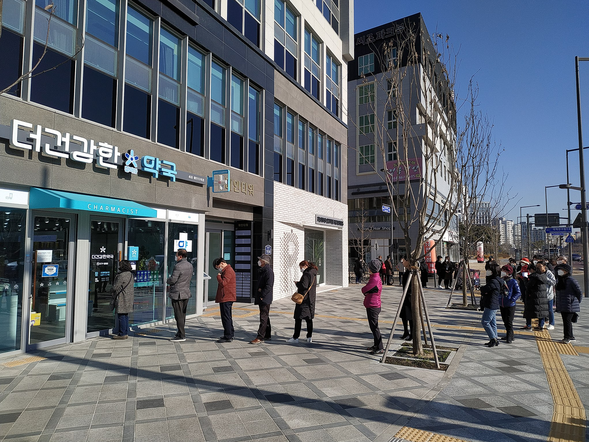 People lined up at a pharmacy to buy masks in Sejong City. Image Credit: Rickinasia on WikiMedia (Created 16 March 2020).