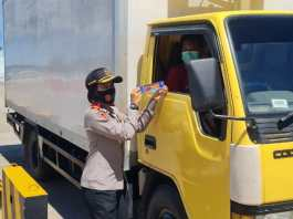 Serdik Sespimmen Polri Dikreg Angkatan 61, Kompol Yunita Stevani, memasang stiker imbauan larangan mudik disalah satu kendaraan