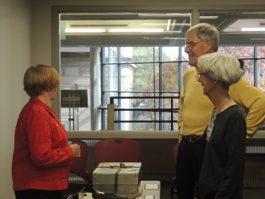 Reference Specialist Becky Jordan discussing artifacts with Life Members of the ISU Alumni Association Andrea and Doug Van Houweling, (Andrea, 1965, chemical technology and Doug, 1965, government). Andrea is the daughter of William Robert Parks, the 11th president of ISU and for whom Parks Library is named
