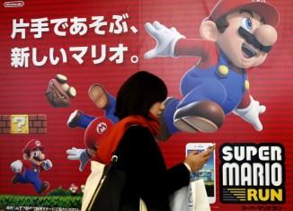 "A woman using a smartphone walks past Nintendo's ""Super Mario Run"" game advertisement board at a subway station in Tokyo, Japan"