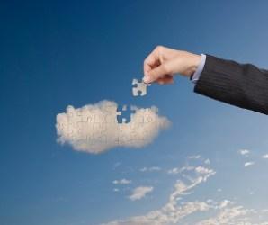 Businessman putting cloud puzzle together