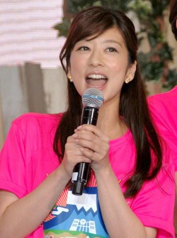 ピンクのTシャツを着てマイクを持ち話すアナウンサー、生野陽子