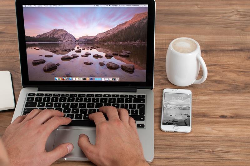 Apple computer on desk with mug and phone