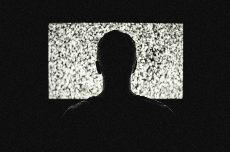 Person Sitting in front of TV Displaying Snow