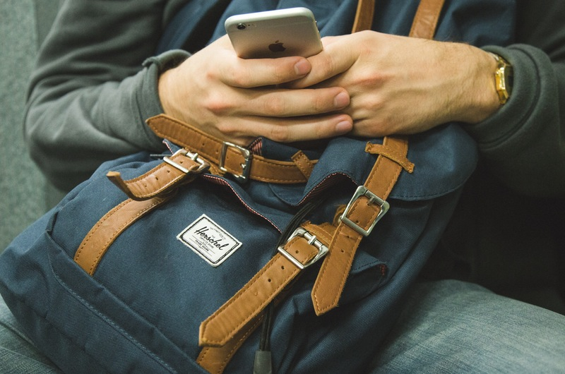 Student with Backpack on Lap looking at Phone