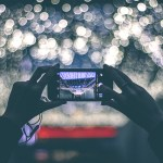 Image of a person taking a photo blurred lights with their phone