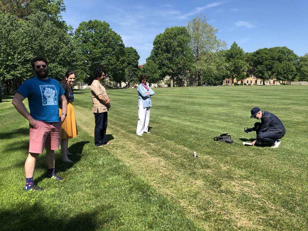 Two menn and two women watching a man ready a drone for flight